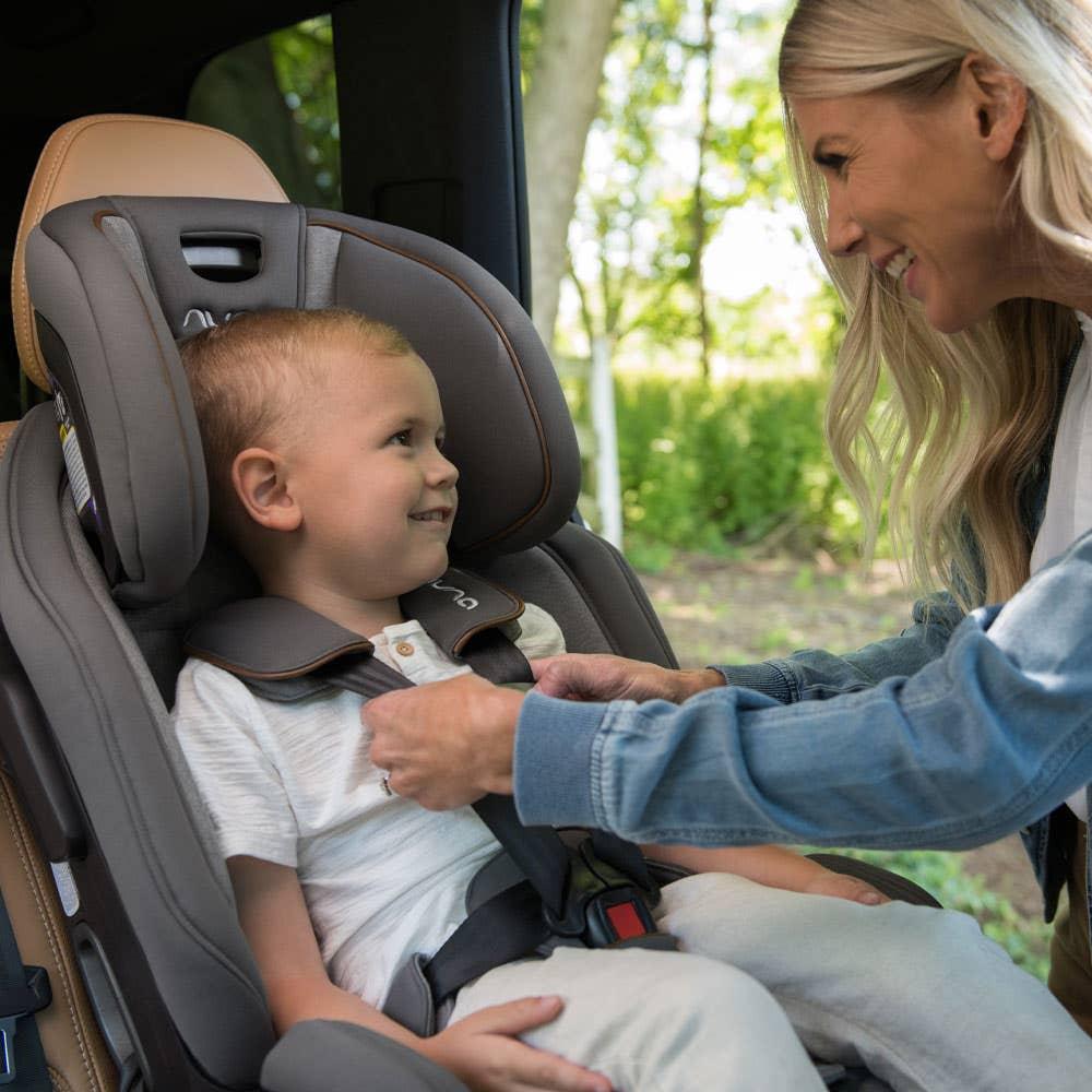 Woman putting child in Nuna EXEC™ car seat