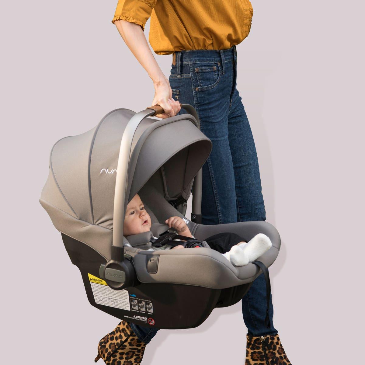 Woman holding Nuna PIPA lite r car seat with baby