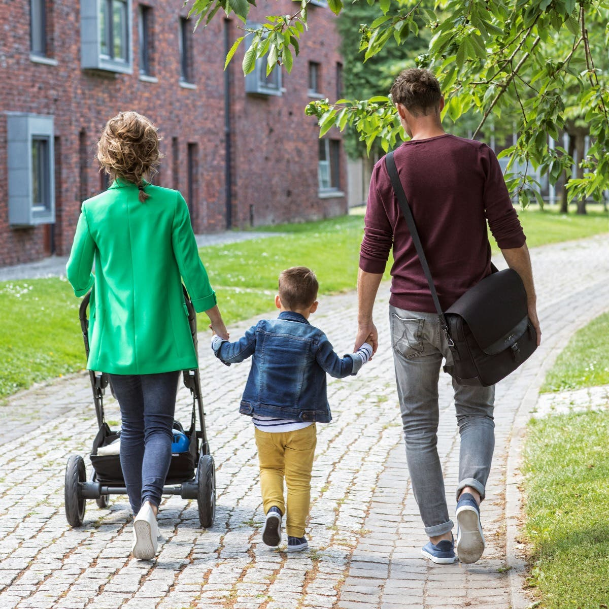Young family walking with dad wearing Nuna diaper bag