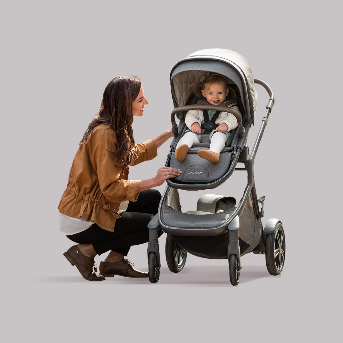 Woman kneeling in front of Nuna stroller with baby