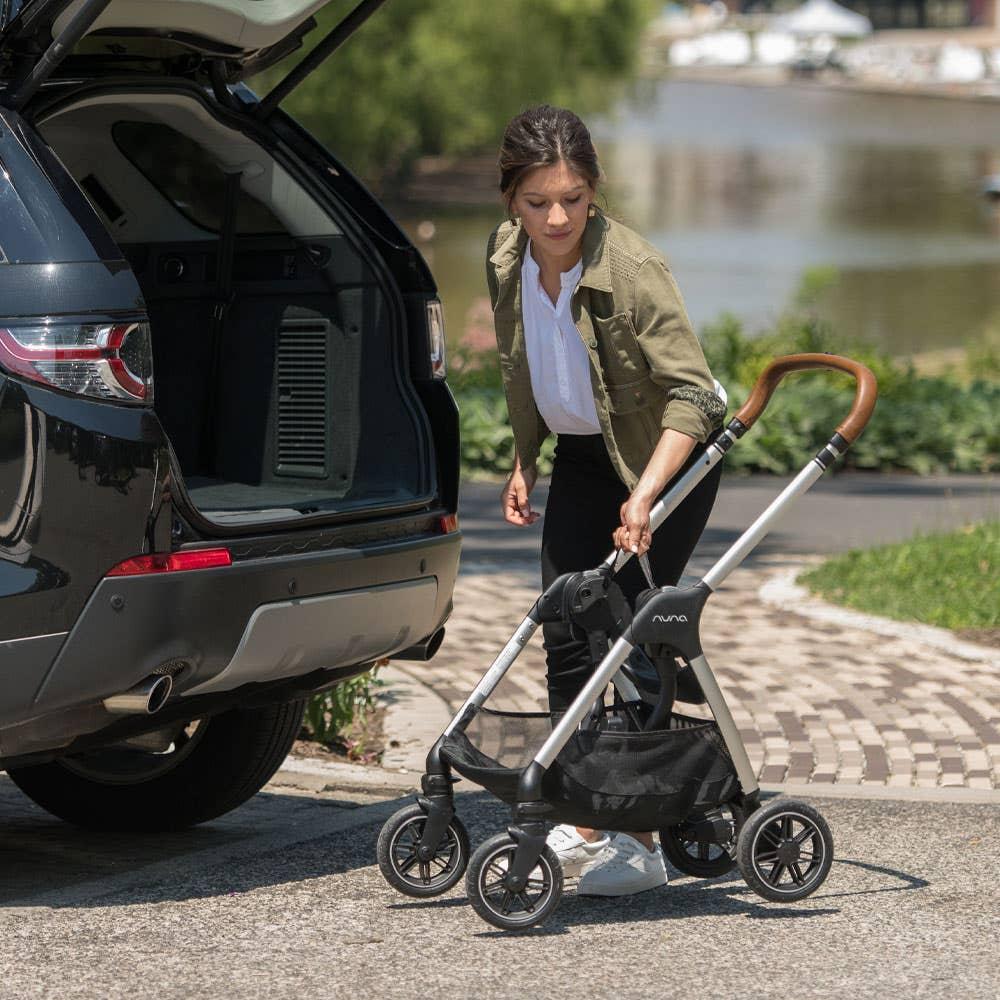 Woman folding Nuna TRIV™ stroller in front of car