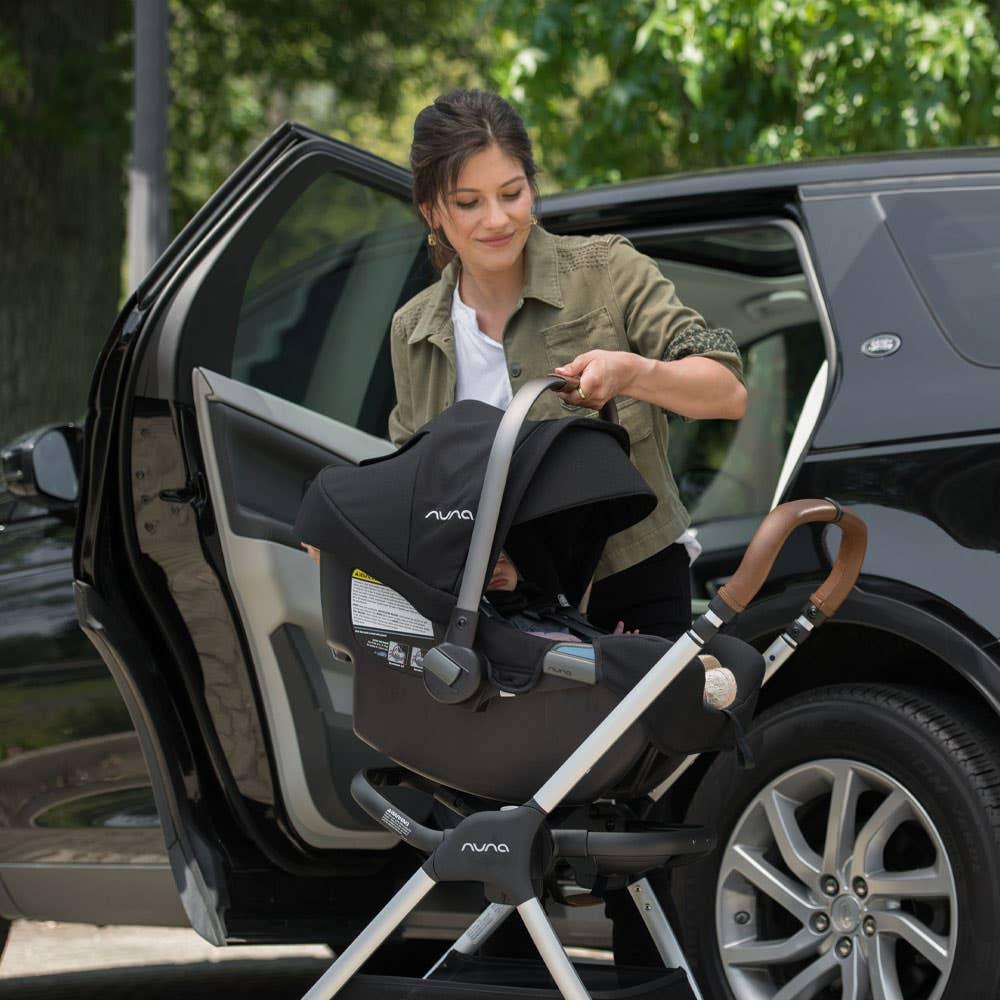 Woman placing Nuna PIPA™ into Nuna TRIV™ stroller